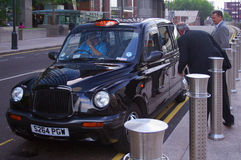 London Taxi. A traditional black London Taxi cab with customers, Canary Wharf Royalty Free Stock Photography