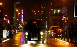 A london taxi waits in a wet city scene stock image