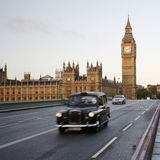 London Taxi on Westminster Bridge. London, UK - October 27, 2012: London Taxi FX4, also called hackney carriage, black cab, Big Ben in the back ground. FX4 is Stock Photography