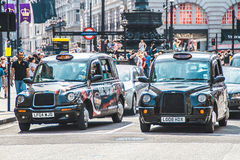 London taxiar på den Piccadilly cirkusen. Royaltyfri Fotografi