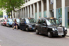 London Taxis. LONDON - JUL 2, 2015: Row of London Taxis lined up along the sidewalk. The London's iconic black cabs are a symbol of the city and a major Royalty Free Stock Photography