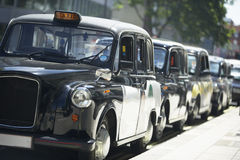 London Taxis Lined Up On Sidewalk Stock Photo