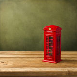 London telephone booth moneybox. On wooden table against grunge background Stock Photo