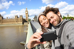 London tourist couple taking photo near Big Ben. Sightseeing women and men having fun using smartphone camera smiling happy near Palace of Westminster Stock Photos