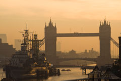 London tower bridge at dawn. HMS Belfast with silhouette tower bridge at dawn royalty free stock images