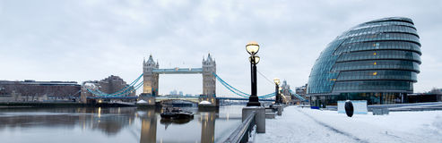 London tower bridge in snow. Tower bridge and city hall by river thames in snow stock image
