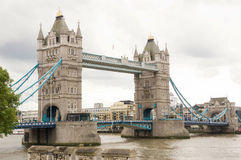 London tower bridge summer view. Full view of tower Bridge London at summer time. one tower closer to the camera then the other one. White sky with some grey Royalty Free Stock Photography