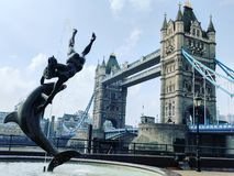 London Tower Bridge. The Tower Bridge, a suspension bridge in London crossing over the River Thames and the Girl with a Dolphin Fountain Stock Photo