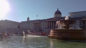 London Trafalgar square fountain with people in slow motion stock video footage