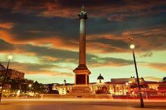 London Trafalgar Square solnedgångNelson kolonn Arkivbild