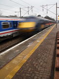 London Trains. Two English Trains speed by one another next to a platform Royalty Free Stock Photo