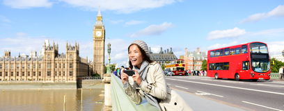 London travel banner - woman and Big Ben. London travel banner with woman tourist, Big Ben and red double decker bus. Girl taking photo on Westminster Bridge royalty free stock photos