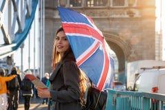 London traveler tourist with a British flag umbrella in London, UK royalty free stock photo
