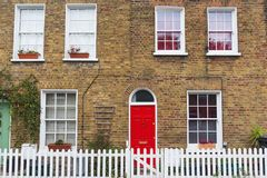 London typical house with brick wall, red door and white fence. London typical old house with brick wall, red door and white fence Stock Image