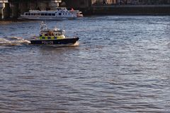 LONDON, UK – Dec 13, 2018: A police boat cutting through the water in a blue bay royalty free stock photo