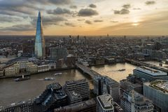 London and Shard from above at sunset. LONDON, UK – FEB 2018: Panoramic aerial view of London with the Shard skyscraper and Thames during sunset. View royalty free stock image