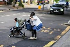 """LONDON UK †""""Maj 14, 2018: Kvinna med barnet i farligt läge, i att korsa den upptagna gatan arkivfoto"""