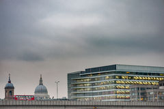 LONDON UK - APRIL 9, 2013: Affärsbyggnadstak med den London bussen på bron arkivbilder