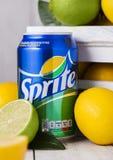 LONDON UK - APRIL 12, 2017: Aluminium can av den Sprite drinken på träbakgrund med citroner och limefrukter Sprite är citron-som  royaltyfria bilder