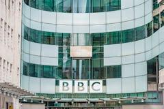 LONDON UK - APRIL 9, 2013: BBChuvudkontor och fyrkant i ormbunksblad av den huvudsakliga ingången arkivfoto