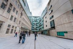 LONDON UK - APRIL 9, 2013: BBChuvudkontor och fyrkant i ormbunksblad av den huvudsakliga ingången med folk royaltyfri fotografi