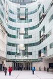 LONDON UK - APRIL 9, 2013: BBChuvudkontor och fyrkant i ormbunksblad av den huvudsakliga ingången med folk royaltyfri foto