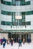 LONDON UK - APRIL 9, 2013: BBChuvudkontor och fyrkant i ormbunksblad av den huvudsakliga ingången med folk arkivbilder