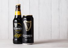LONDON, UK - APRIL 27, 2018: Bottle and aluminium can of Guinness draught stout beer  bottle on light wooden background. LONDON, UK - APRIL 27, 2018: Bottle and Royalty Free Stock Photography