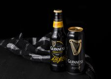 LONDON, UK - APRIL 27, 2018: Bottle and aluminium cans of Guinness draught stout beer  bottle on dark wooden background. LONDON, UK - APRIL 27, 2018: Bottle and Royalty Free Stock Photo