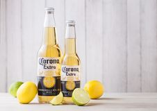 LONDON, UK - APRIL 27, 2018: Bottles of Corona Extra Beer on wooden background with fresh lemons and limes . Corona, produced by Grupo Modelo stock images