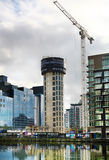LONDON, UK - APRIL 24, 2014: Building site with cranes in Canary Wharf aria. Raising new tallest residential tower Royalty Free Stock Photo