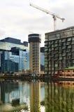 LONDON UK - APRIL 24, 2014: Byggnadsplats med kranar i den Canary Wharf arian Lyfta det nya mest högväxta bostads- tornet Arkivbild
