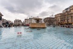 LONDON UK - APRIL 9, 2013: Den Trafalgar Square springbrunnen med många personer och sighten turnerar av den London bussen i bakg arkivbilder