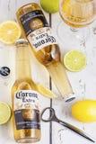 LONDON UK - APRIL 27, 2018: Glasflaskor av Corona Extra Beer på ljus träbakgrund med flasköppnaren och exponeringsglas av öl royaltyfri fotografi