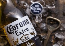 LONDON, UK - APRIL 27, 2018: Glass Bottle of Corona Extra Beer on wooden background with bottle opener and ice cubes.Top view. LONDON, UK - APRIL 27, 2018: Glass stock images