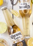 LONDON, UK - APRIL 27, 2018: Glass Bottles of Corona Extra Beer on light wooden background with bottle opener and glass of beer.To. LONDON, UK - APRIL 27, 2018 royalty free stock photo