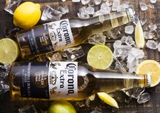 LONDON, UK - APRIL 27, 2018: Glass Bottles of Corona Extra Beer on wooden background with ice cubes and fresh lemons.Top view. LONDON, UK - APRIL 27, 2018: Glass stock photography
