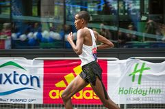 Professional sprinter arriving the first in Canary Wharf.. London, UK. London, UK - April 23, 2017: London Marathon. Professional sprinter arriving the first in Stock Image