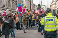London, UK - April 15, 2019: Metropolitan Police officers patrols at Oxford street. Extinction Rebellion campaigners barricade at. Oxford Circus, The royalty free stock photos