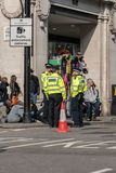 London, UK - April 15, 2019: Metropolitan Police officers patrols at Oxford street. Extinction Rebellion campaigners barricade at. Oxford Circus, The stock photography