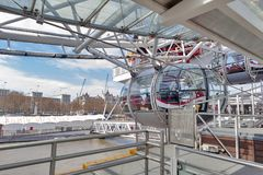 Passenger capsule arriving at boarding platform of the London Eye in London, England. London, UK - April 2018: Ovoidal passenger capsule arriving at boarding Stock Images
