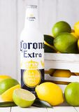 LONDON, UK - APRIL 27, 2018: Steel Bottle of Corona Extra Beer on wooden background with fresh lemons and limes in wooden box. LONDON, UK - APRIL 27, 2018 royalty free stock photo