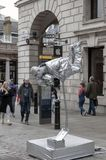 Street artist painted in silver performing physical magic at Covent Garden, London, UK stock photos