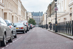 LONDON, UK - APRIL 9, 2013: Street with only one person. Only parking cars and road signs Royalty Free Stock Images