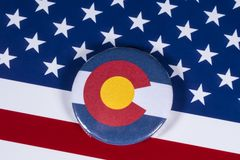 State of Colorado in the USA. LONDON, UK - APRIL 27TH 2018: The symbol of the State of Colorado, pictured over the flag of the United States of America, on 27th stock photography