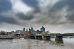 LONDON UK - APRIL 9, 2013: Thames River med färjan och affärsmitten i bakgrund molnig dag royaltyfri fotografi
