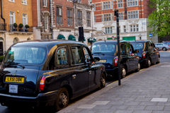 LONDON, UK - April 14, 2015: three London vintage cabs waiting in the street Stock Images