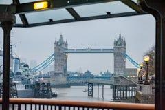LONDON UK - APRIL 9, 2013: Tornbro med krigsskeppet i Thames River Fotofors för sen afton royaltyfri foto