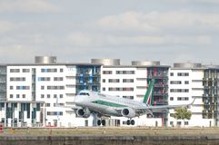 Alitalia airplane land at London City Airport, the fifth busiest airport in London. LONDON, UK - AUGUST 02, 2013: Alitalia airplane land at London City Airport stock photography