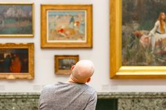 Back view of a bald man admiring paintings displayed at Tate Britain. London, UK - August 15, 2017 - Back view of a bald man admiring paintings displayed at Tate royalty free stock images
